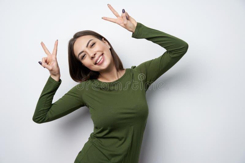 打手势和平标志微笑的愉快的深色的妇女 库存照片