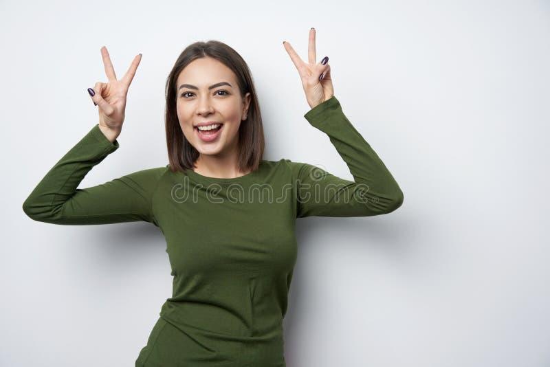 打手势和平标志微笑的愉快的深色的妇女 库存图片