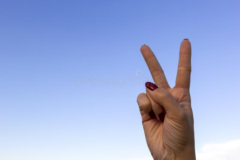 打手势和平标志或胜利在天空蔚蓝背景的手 库存图片