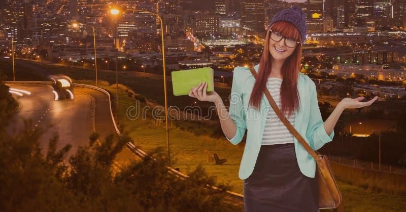 打手势和拿着有吊索袋子的美丽的妇女绿色钱包站立反对路照亮 免版税图库摄影