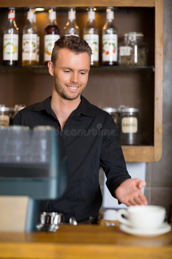 打手势在柜台的Barista在Coffeeshop 免版税图库摄影