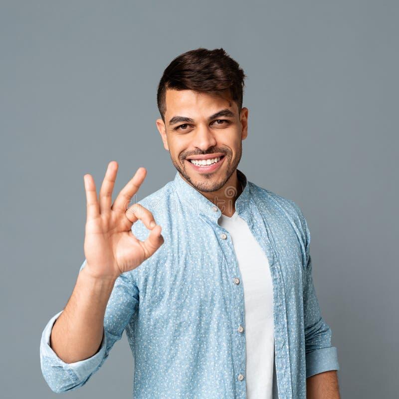 打手势在灰色背景的微笑的阿拉伯人OK标志 免版税库存照片