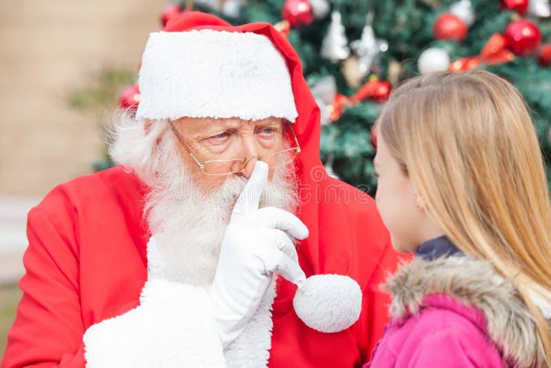 打手势在嘴唇的圣诞老人手指,当看时 库存图片