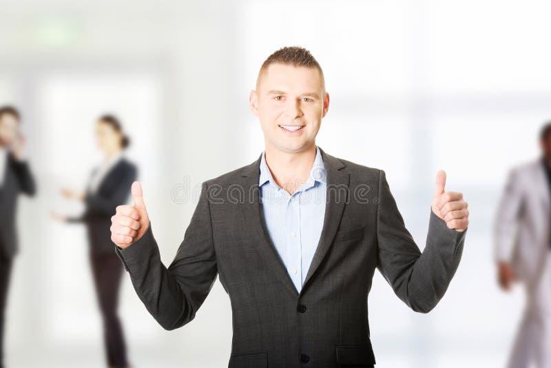 打手势好标志的年轻商人 免版税图库摄影