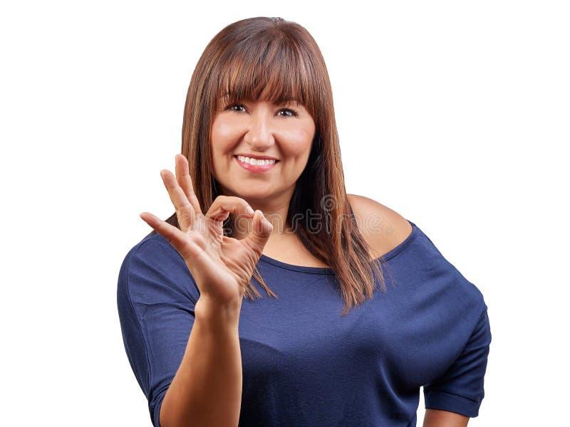 打手势好象标志的微笑的深色的妇女被隔绝 免版税库存图片