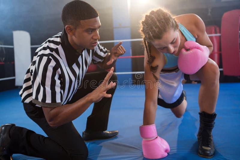 打手势对圆环的女性拳击手的裁判员 库存照片