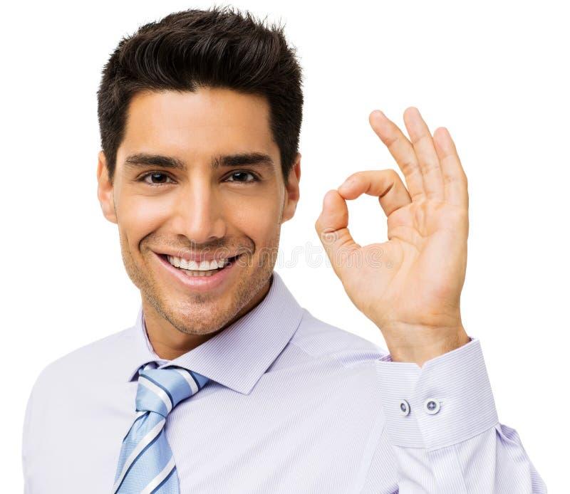 打手势微笑的商人好 免版税库存照片