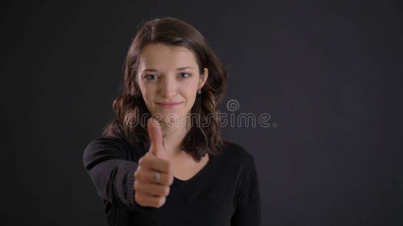 打手势手指在黑背景的逗人喜爱的年轻深色的妇女画象标志微笑地显示象和尊敬 免版税库存照片