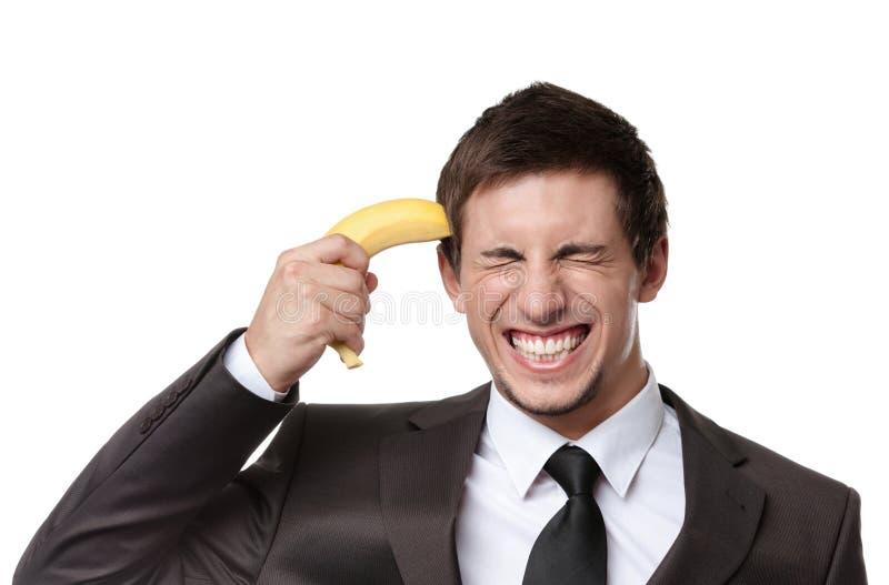 打手势枪用香蕉的商人 免版税图库摄影