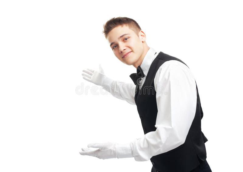 打手势欢迎的年轻愉快的微笑的侍者 免版税库存照片