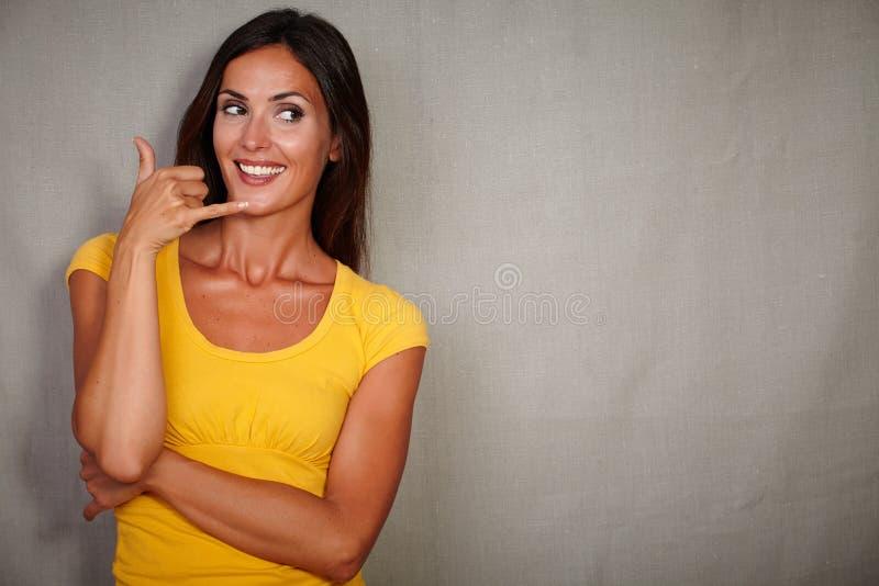 打手势电话的漂亮的女人,当微笑时 库存照片