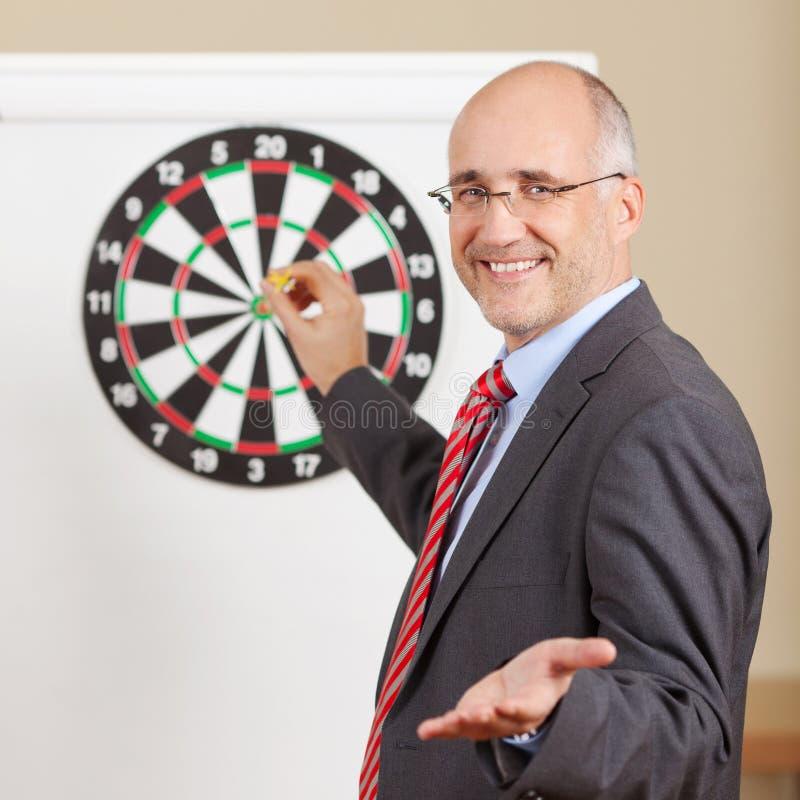 打手势的商人,当拿着箭附有在F时的目标 免版税库存照片