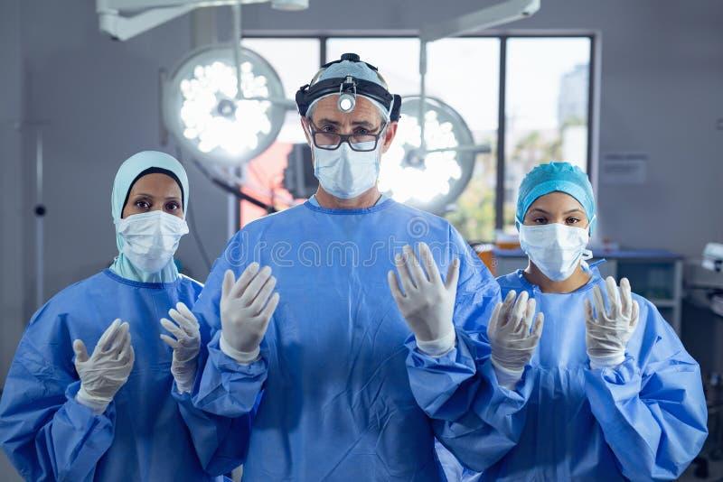 打手势的外科医生,当站立在手术室在医院时 图库摄影