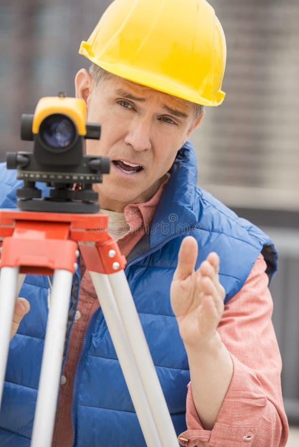 打手势的测绘员,当使用经纬仪时 免版税库存照片
