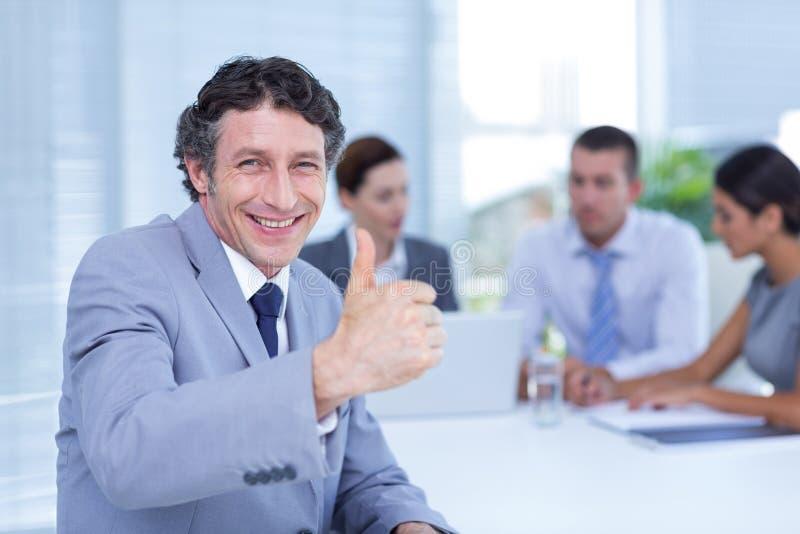 打手势赞许的微笑的商人 图库摄影