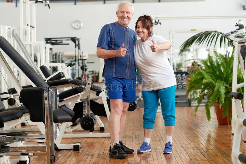 打手势赞许的成熟夫妇在健身房 免版税库存照片