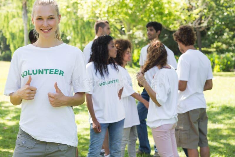 打手势赞许的美丽的志愿者 库存图片