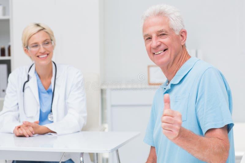 打手势赞许的资深患者,当看他时的医生 库存图片