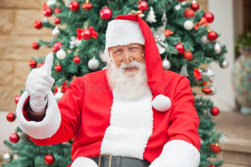 打手势Thumbsup的圣诞老人反对圣诞节 库存图片