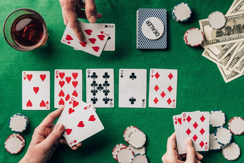 打扑克的人们由与卡片的赌博娱乐场桌 库存照片