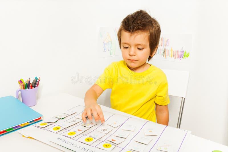打指向日历的男孩在开发的比赛 库存图片