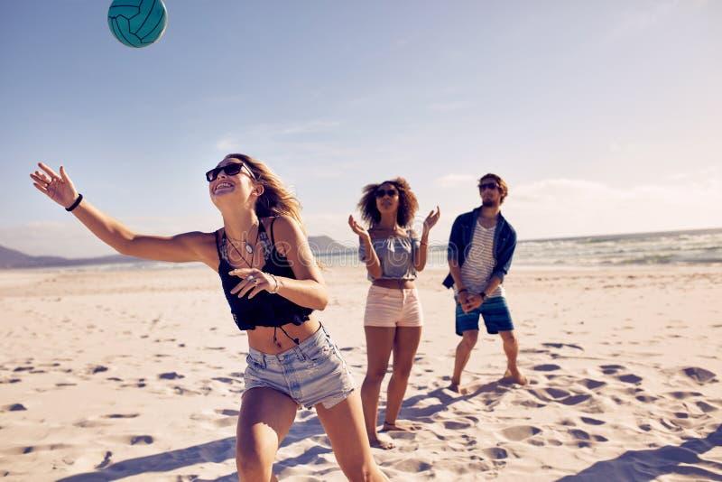 打排球的海滩朋友 免版税图库摄影