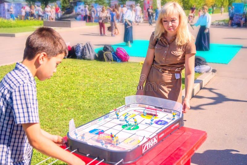 打桌曲棍球的妈妈和儿子少年在公园在一个晴朗的夏日 免版税库存图片