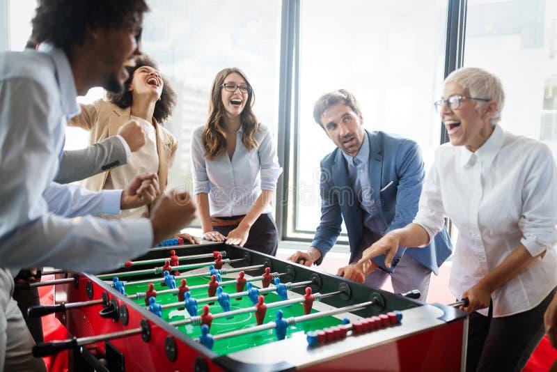 打桌足球室内比赛的雇员在办公室在休息时间 图库摄影