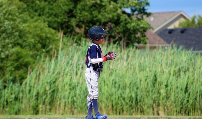 打棒球的英俊的逗人喜爱的年轻男孩等待和保护基地 库存照片