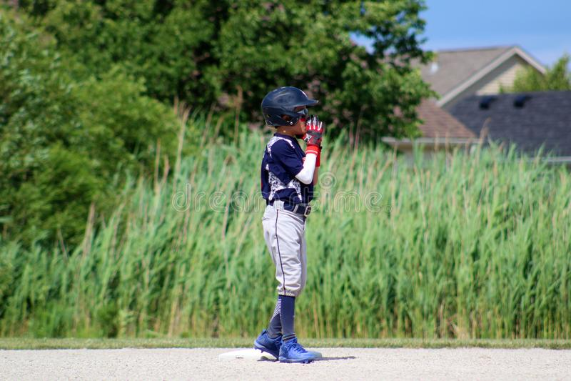 打棒球的英俊的逗人喜爱的年轻男孩等待和保护基地 图库摄影