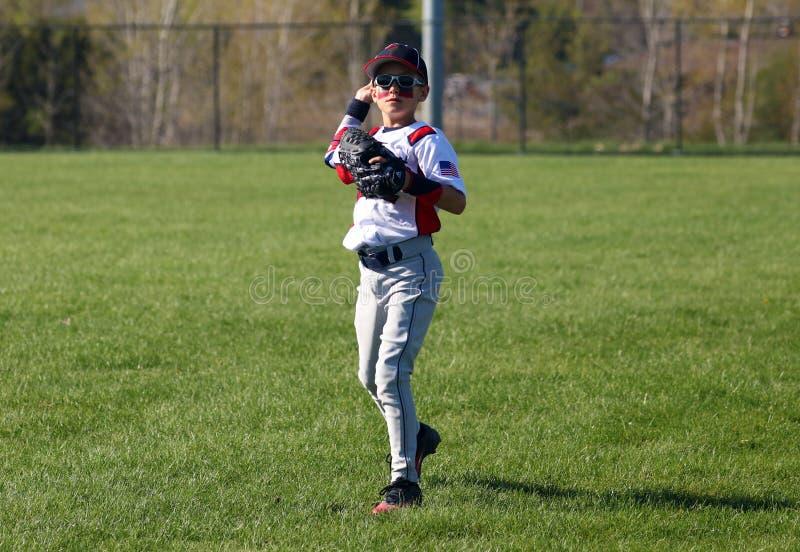 打棒球的英俊的逗人喜爱的年轻男孩等待和保护基地 免版税库存照片