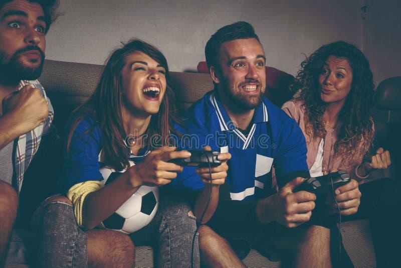 打橄榄球电子游戏的朋友 免版税库存图片
