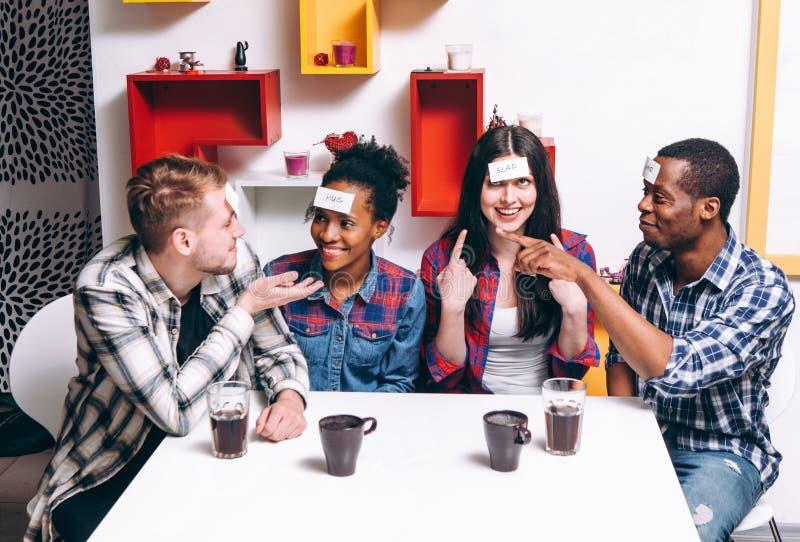 打比赛猜测谁是我,四个朋友获得乐趣 免版税库存照片