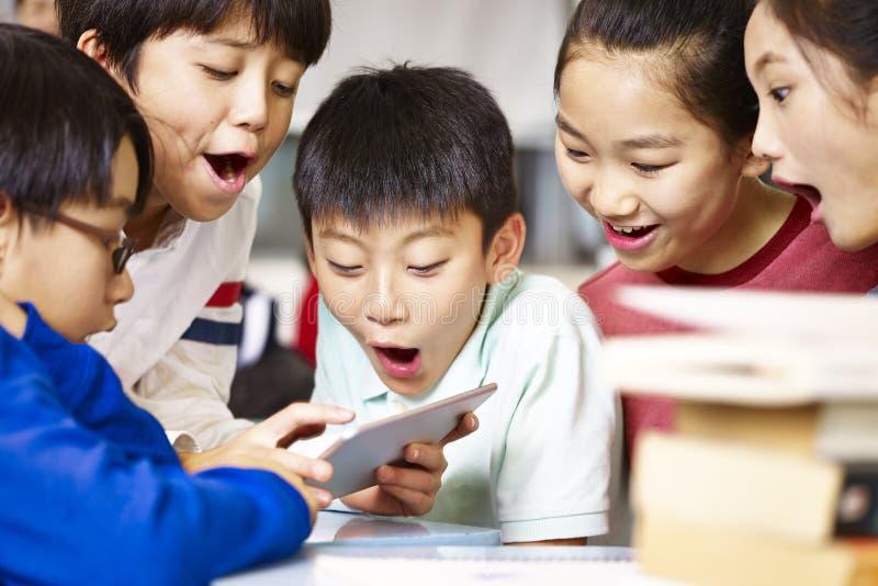 打比赛的小组亚洲小学学生使用片剂 免版税库存照片