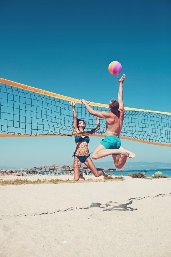 打沙滩排球的人们获得乐趣在运动的活跃生活方式 在夏天供以人员击中在比赛的齐射球 妇女 免版税库存照片