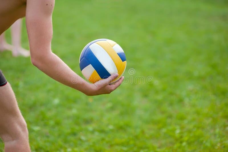打沙滩排球的青少年的男孩 使用与球,排球球的草的排球运动员在他的手上 库存照片