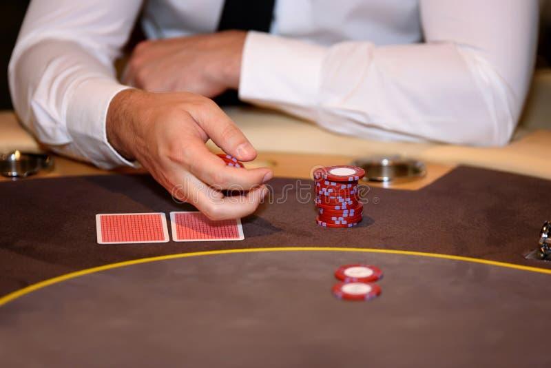 打牌者的手特写镜头有芯片和卡片的在啤牌t 免版税库存照片