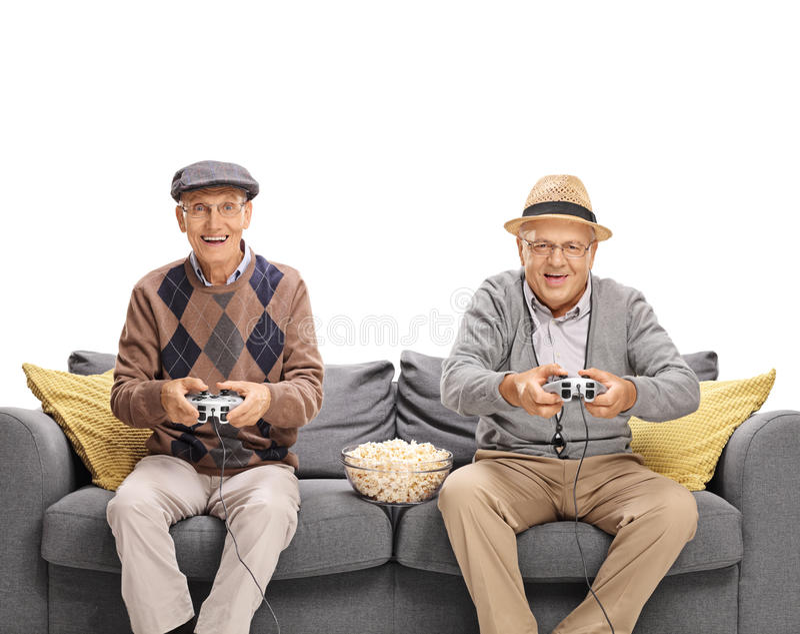 打电子游戏的两个快乐的前辈 免版税库存图片