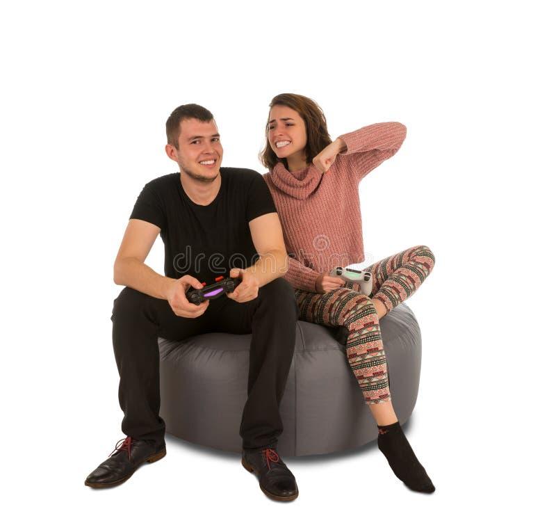 年轻打电子游戏的人和妇女,当坐圆的s时 库存照片