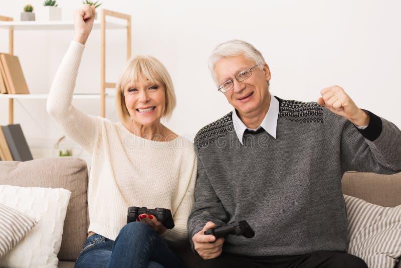打电子游戏的年长夫妇,庆祝胜利 图库摄影
