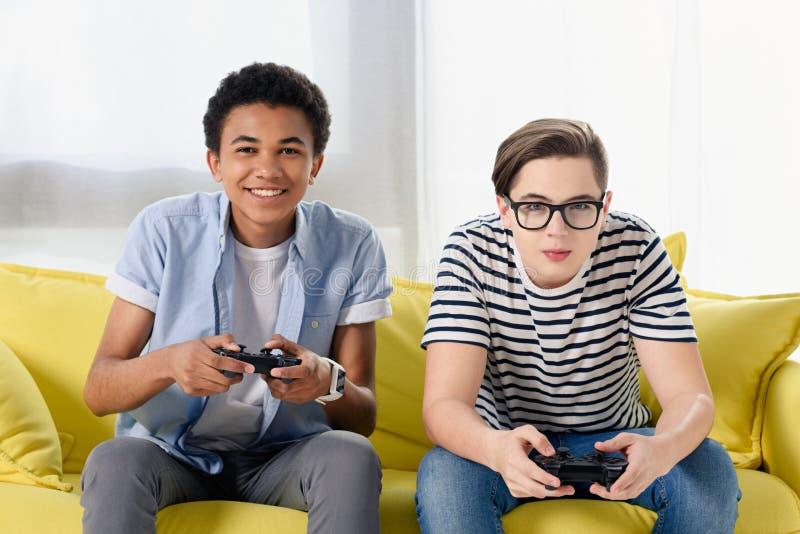 打电子游戏的愉快的多文化青少年的男孩 图库摄影