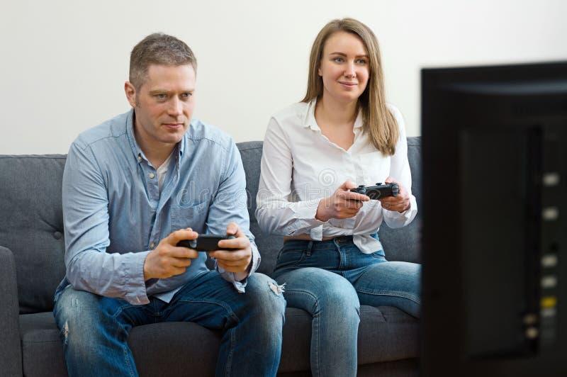 打电子游戏的男人和妇女 免版税库存图片