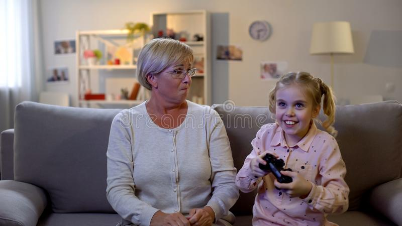 打电子游戏,生气老婆婆的愉快的女孩羡慕看孙女 图库摄影