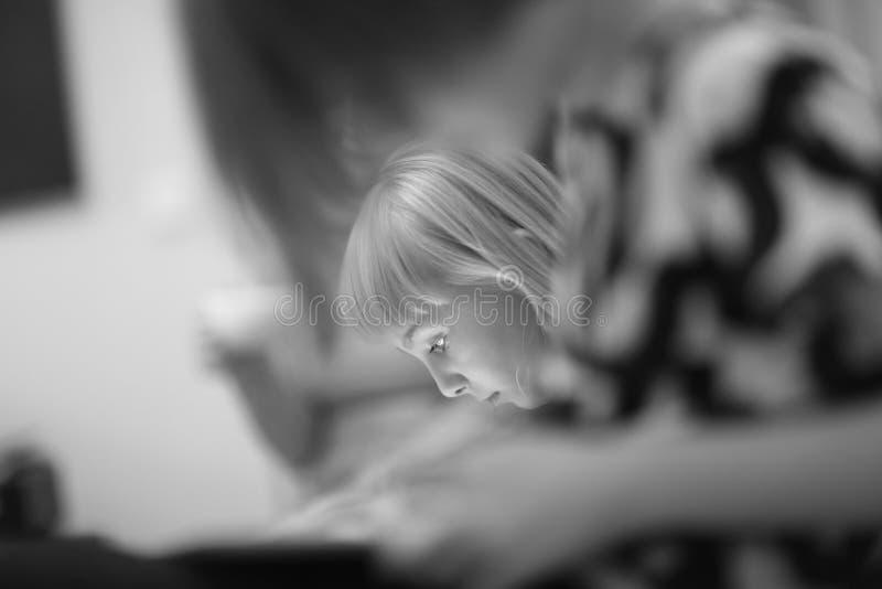 打电脑游戏的一个逗人喜爱的白肤金发的女孩的面孔 免版税图库摄影