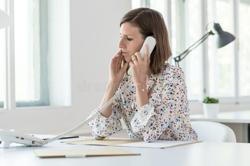 打电话的严肃的年轻女商人 免版税库存照片