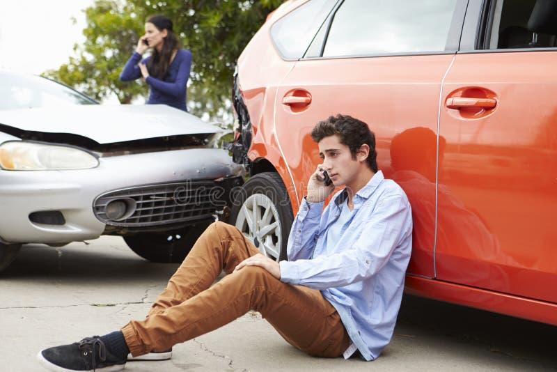打电话的少年司机在交通事故以后 库存照片