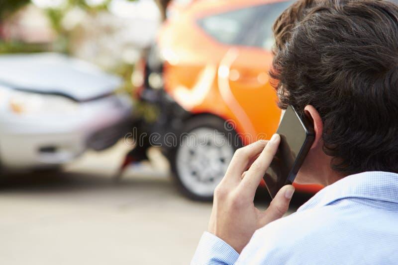 打电话的少年司机在交通事故以后 免版税库存照片