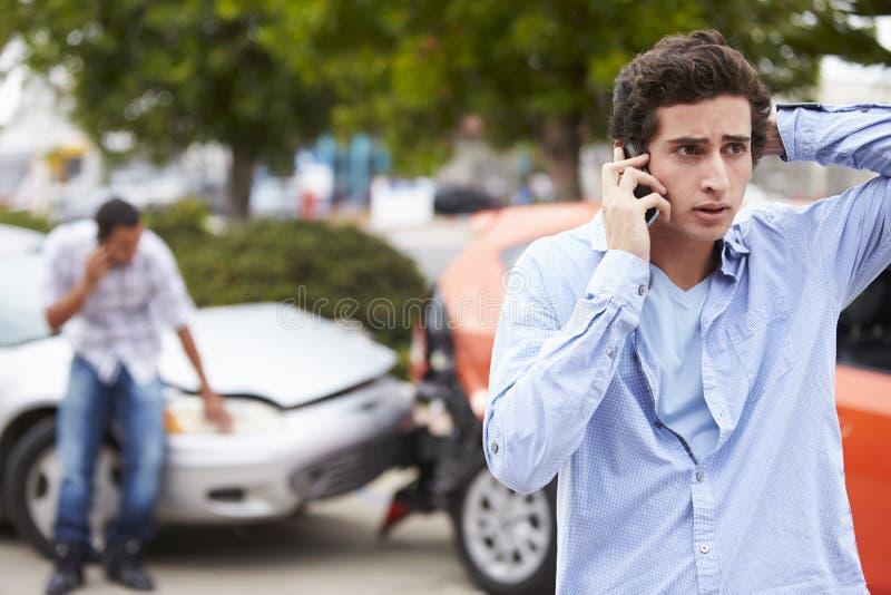 打电话的少年司机在交通事故以后 免版税库存图片
