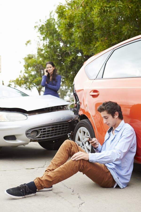 打电话的少年司机在交通事故以后 免版税图库摄影