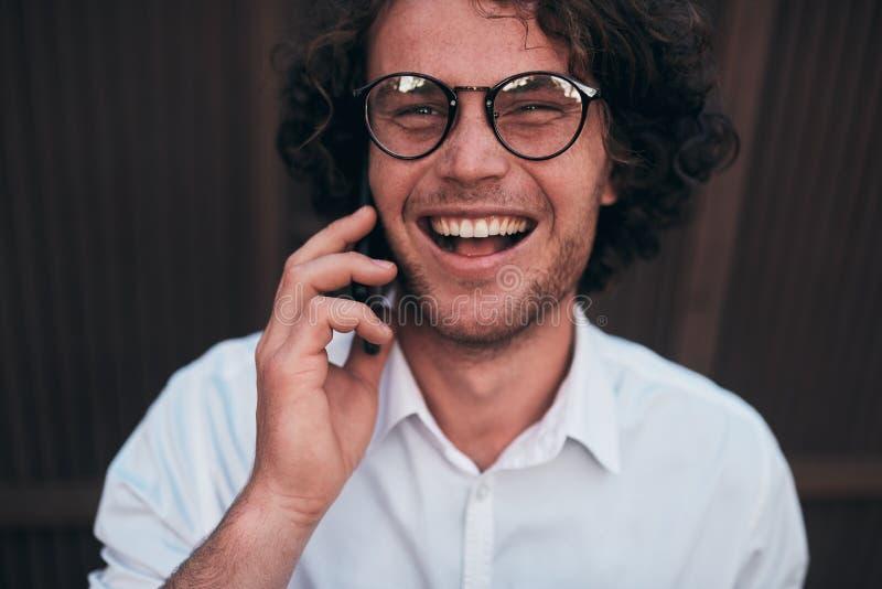 打电话的愉快的英俊的年轻商人特写镜头画象,当走户外佩带的白色衬衫和眼镜时 免版税库存照片